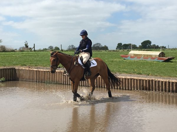 Charlotte riding Oggie through the water on a cross country course